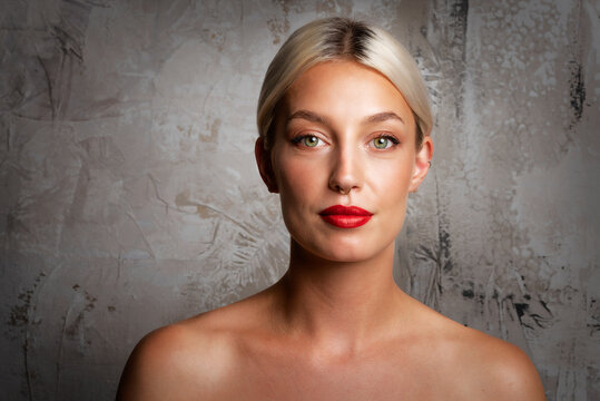 Headshot of blond haired woman wearing red lipstick while standing at grey background