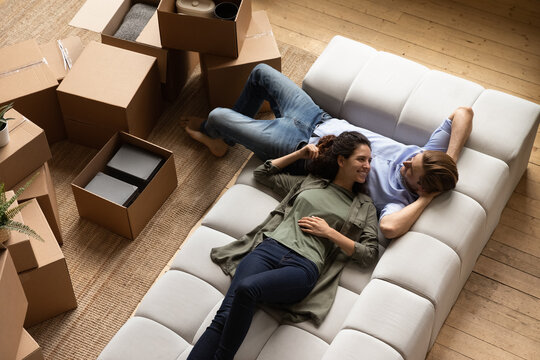 Smiling millennial family couple resting on cozy couch, renewing energy after moving cardboard boxes in new apartment, planning future decorations or discussing interior ideas together at home.