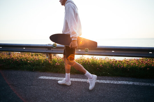 Cool young millennial man walk with longboard on sunny summer sunset evening with light leaks going into lens. Generation z trendy youth. Use skateboard for commute in city. Wanderlust travel