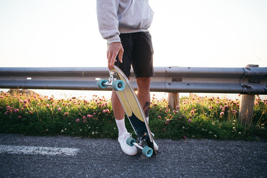 Cool trendy young unrecognizable man stand on sunny street and hold cruiser skateboard. Modern millennial man with longboard. Summer youth vibes, forever young. Generation z teenager