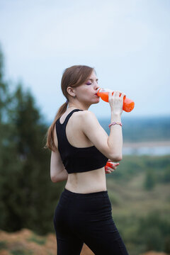 Woman wearing sportswear hydrating herself drinking vibrant orange juice during workout. Evening or morning time in the nature