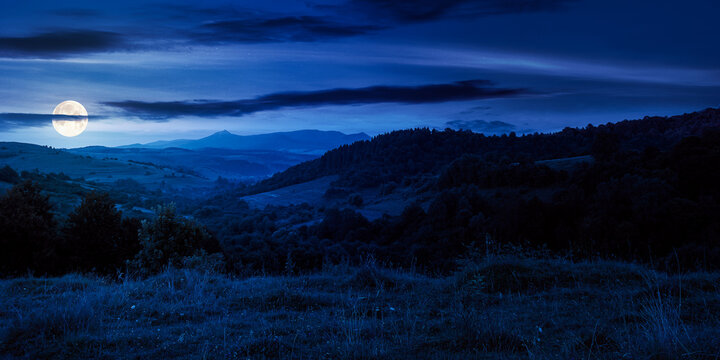 mountainous countryside landscape at night. pastures and rural fields near the forest on the hills. beautiful early autumn nature scenery with clouds on the sky in full moon light