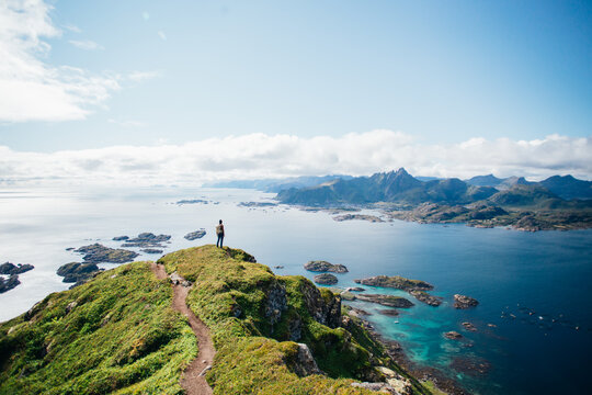 Amazing epic shot of young man hiker stand on top of mountain after long difficult hike in Lofoten Islands in Norway. Incredible summer views of scandinavian travel lifestyle. Epic landscape in north