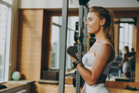 Side view smiling young strong skinny sporty athletic sportswoman woman 20s wearing white sportswear warm up training do dummbells exercises in gym indoor Workout sport motivation lifestyle concept.