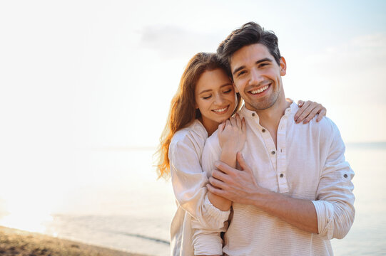 Romantic charming sunlit smiling happy young couple two friends family man woman in casual clothes hug each other at sunrise over sea beach ocean outdoor exotic seaside in summer day sunset evening.