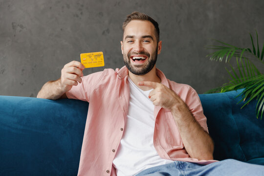 Young smiling happy fun man 20s in casual clothes point index finger on credit bank card sitting on blue sofa at home flat indoors rest relax on weekends free time. People lounge lifestyle concept