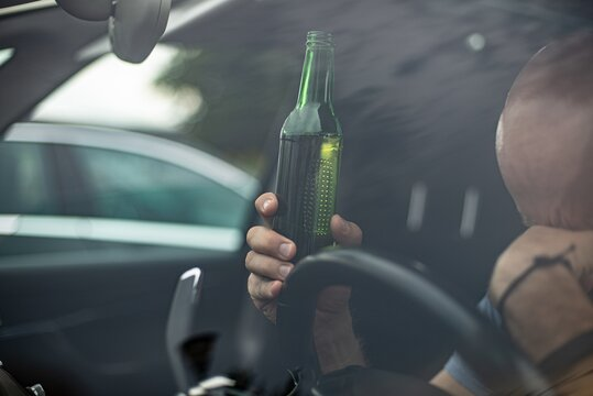 Sad man is caught driving under alcohol influence. Man holding beer bottle behind the wheel.