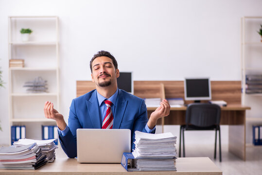 Young male employee unhappy with excessive work at workplace