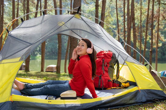 Woman Enjoy listening to music from headphones. She sat in a yellow tent. beside Lake, Pang Oung, Mae Hong Son, Thailand