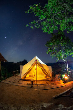 Bell tent camping white in the midst of nature and the Milky Way at night.
