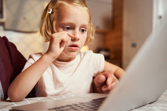 Girl scratching her nose while working at laptop