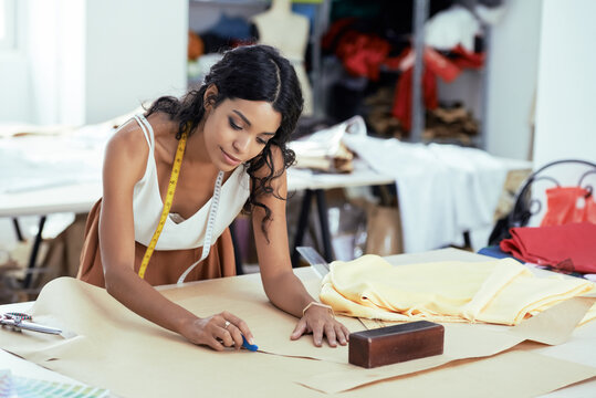 Talented creative young garment designer working on pattern for new dress