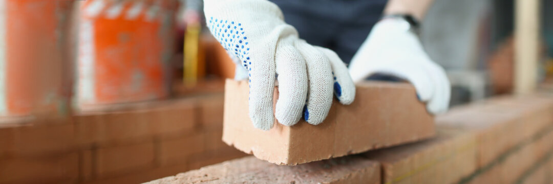 Man builder in protective gloves is building wall of bricks closeup
