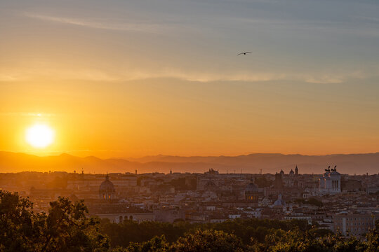 The sun is rising over the center of Rome full of ancient buildings and monuments
