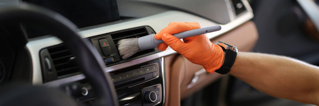 Male hand hold grey blush in orange protective gloves