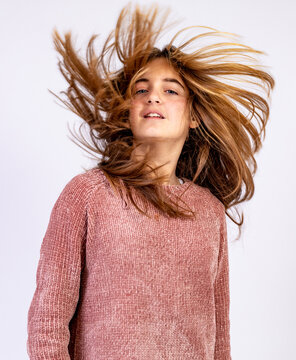 Young smiling girl shaking her head with hair dishevelled by the wind in a glamorous pose