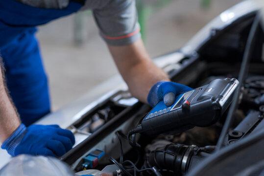 Mechanic using a battery tester