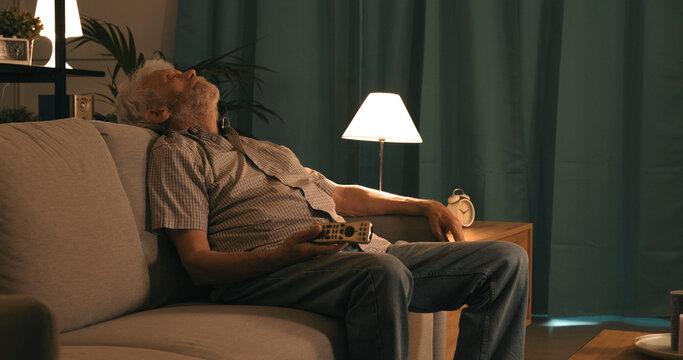 Senior man falling asleep while watching TV
