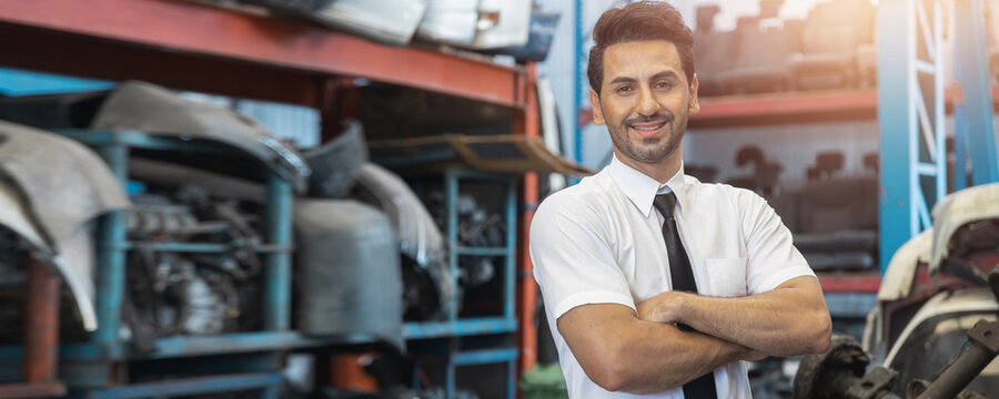 Portrait of man crossing arm and smiled in factory of old auto spare parts