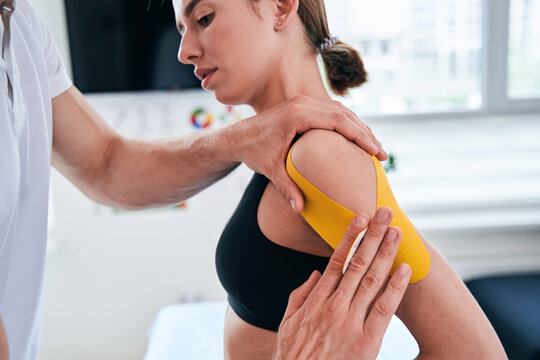 Unrecognized manual therapist taping yellow tape on patient shoulder in wellness center