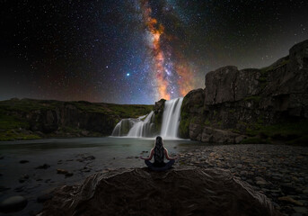 Obraz Woman doing yoga in front of a magic waterfall - fototapety do salonu