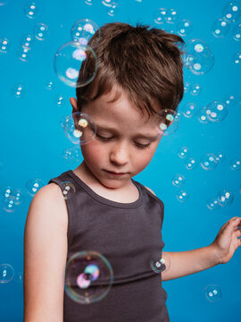 Child looking away in studio with soap bubbles