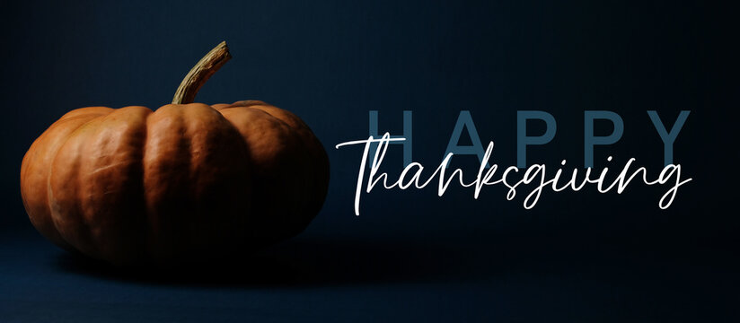 Fall holiday banner with lettering by pumpkin decoration and happy thanksgiving text on dark background.