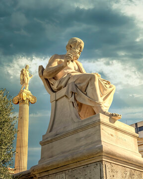 Plato, the ancient Greek philosopher and Apollo god marble statues under dramatic cloudy sky