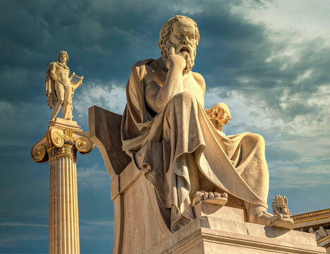 Socrates the ancient Greek philosopher and Apollo god marble statues under dramatic sky