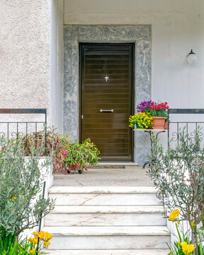 contemporary family house white marble stairs with colorful potted flowers to entrance door