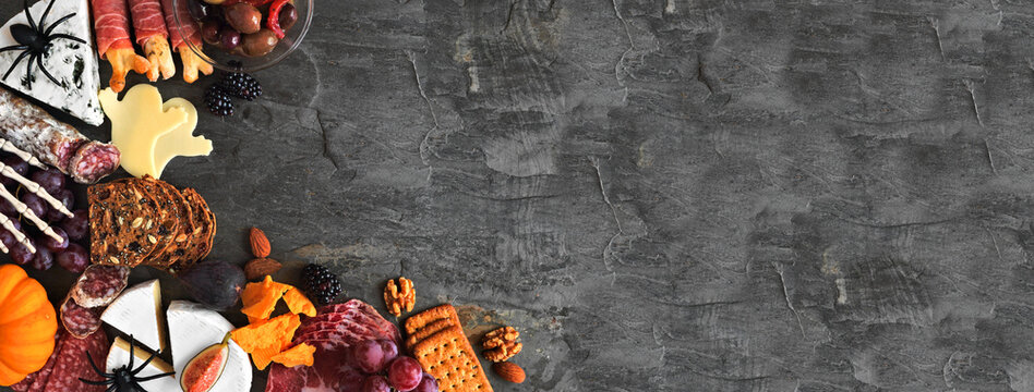 Halloween themed charcuterie corner border against a dark stone banner background. Variety of cheese and meat appetizers. Copy space.