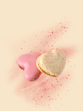 Two sweet macarons in heart shape flying isolated on pink yellow background. French macaron cookies with raspberry and vanilla.