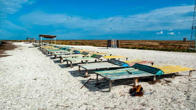 An abandoned beach with old wooden sun beds