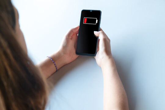 Low Battery on smartphone in the hands of a young teenager girl. Tired student. Mobile phone off.