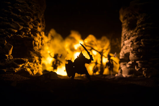 Medieval battle scene with cavalry and infantry. Silhouettes of figures as separate objects, fight between warriors on dark toned foggy background with medieval castle.