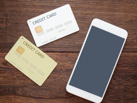 テーブルの上のスマートフォンと2枚のクレジットカード