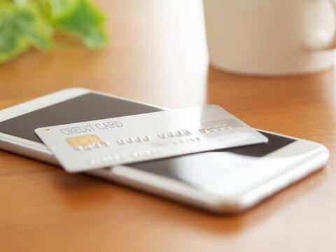 テーブルの上のスマートフォン、クレジットカード、コーヒーカップ