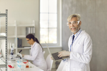 Science, medicine, technology, biology and people. Portrait of a doctor scientist working in a research laboratory holding a laptop in his hands. Scientist makes notes on the study on a computer.