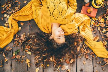 Obraz Young beautiful woman lies on autumn foliage in the park. - fototapety do salonu