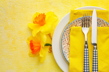 Beautiful table setting with narcissus flowers on color background
