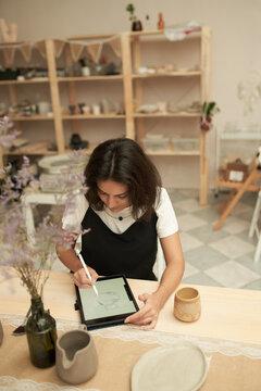 Pottery designer sketching on tablet