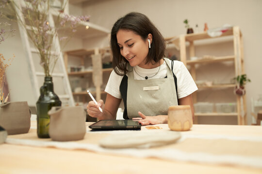 Ceramist with tablet and earbuds working in studio