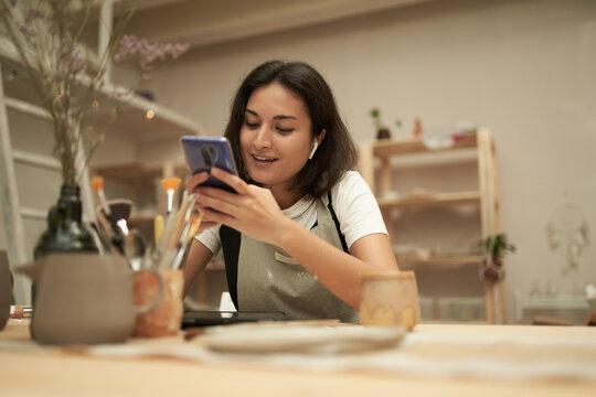 Happy craftswoman texting on smartphone