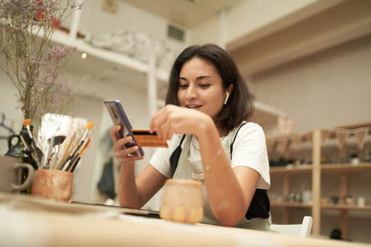 Craftswoman paying for online order with credit card