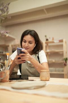 Craftswoman using mobile phone in studio