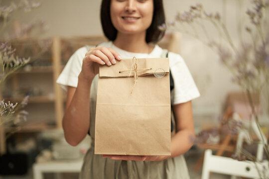 Crop craftswoman demonstrating paper bag