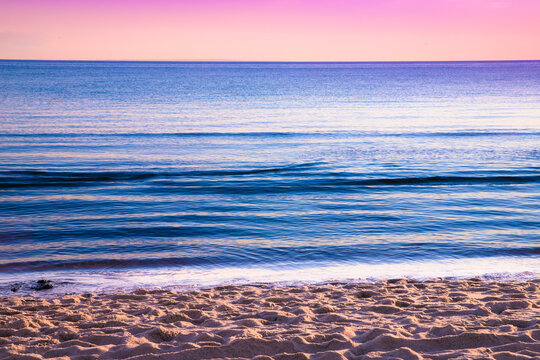 View from beach at sunset with ocean, colorful sky and sea