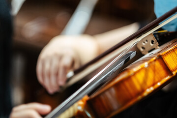 Closeup of a musician playing violin at the concert, focus on the violi