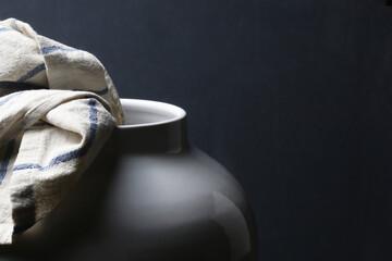 Un vaso in ceramica bianca e uno strofinaccio da cucina; composizione su fondo scuro