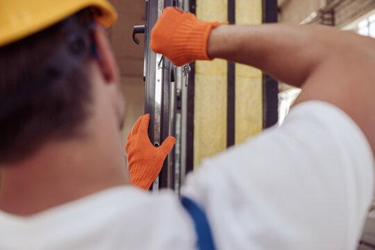Male worker repairing door in building under construction